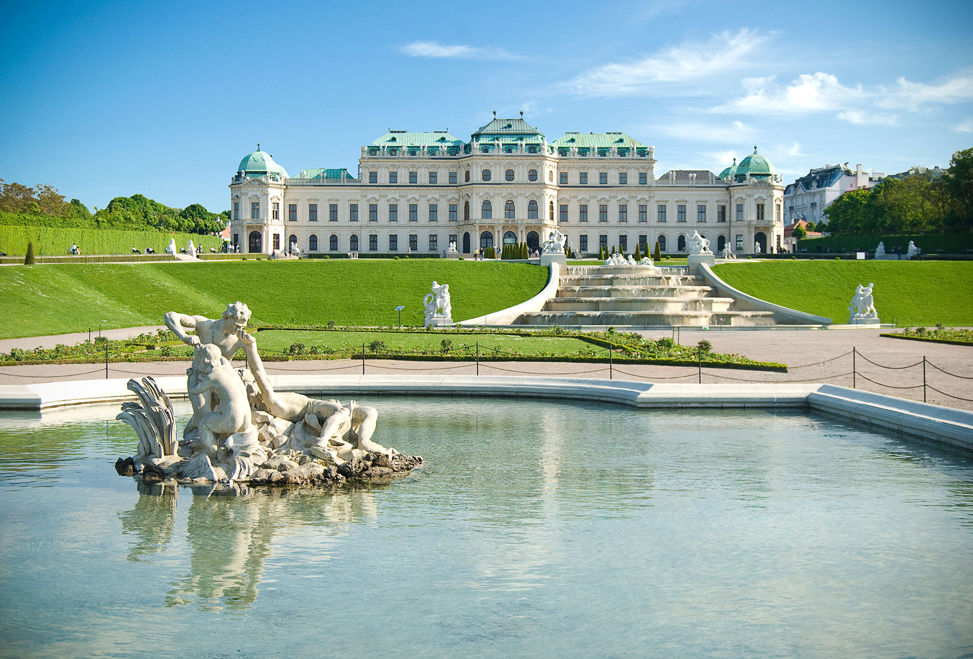 a small boat in a body of water with Belvedere, Vienna in the background