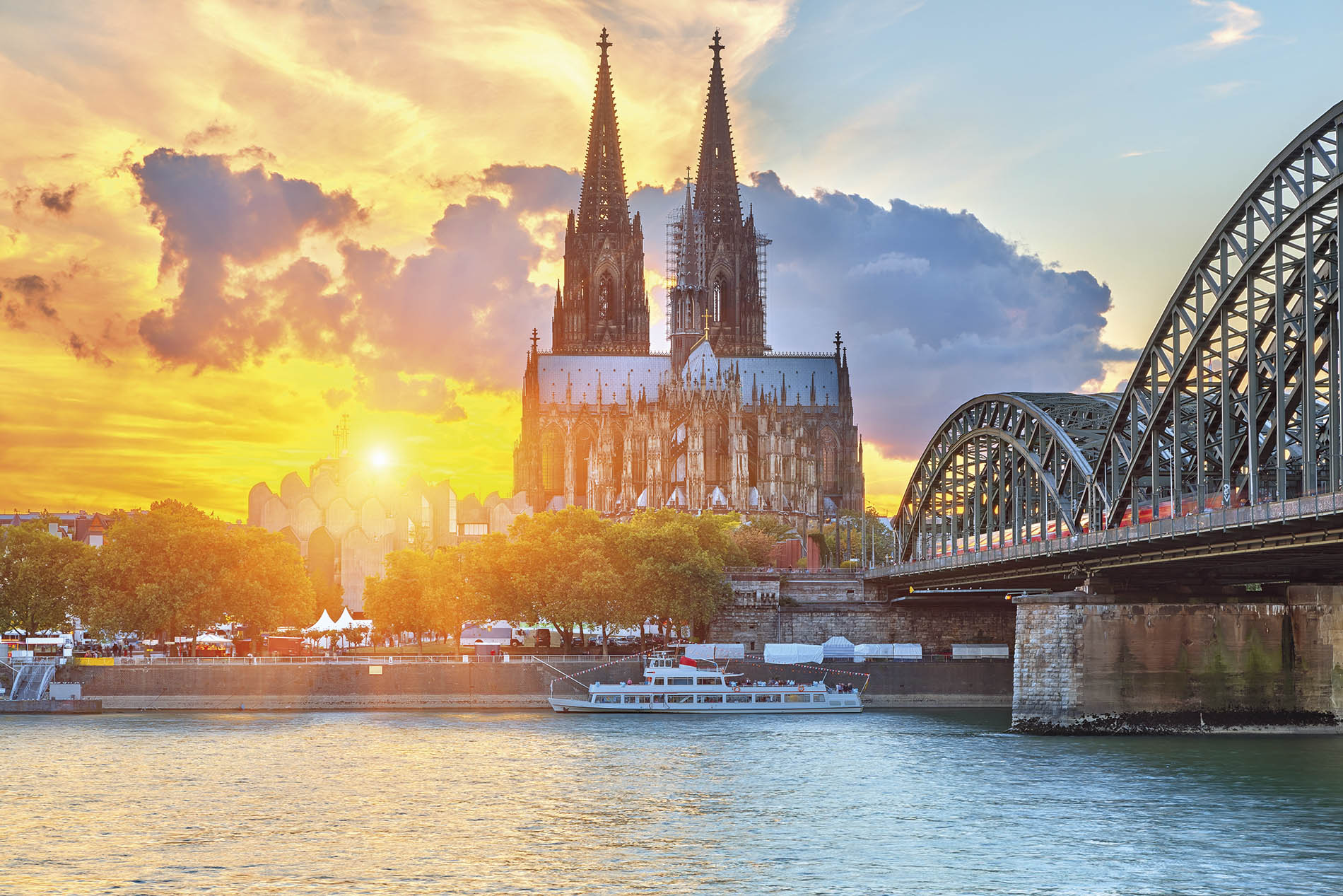 a large bridge over a body of water with Cologne Cathedral in the background