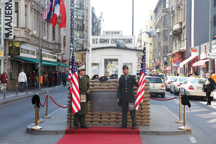 Two soldiers holding the US flag at Checkpoint Charlie